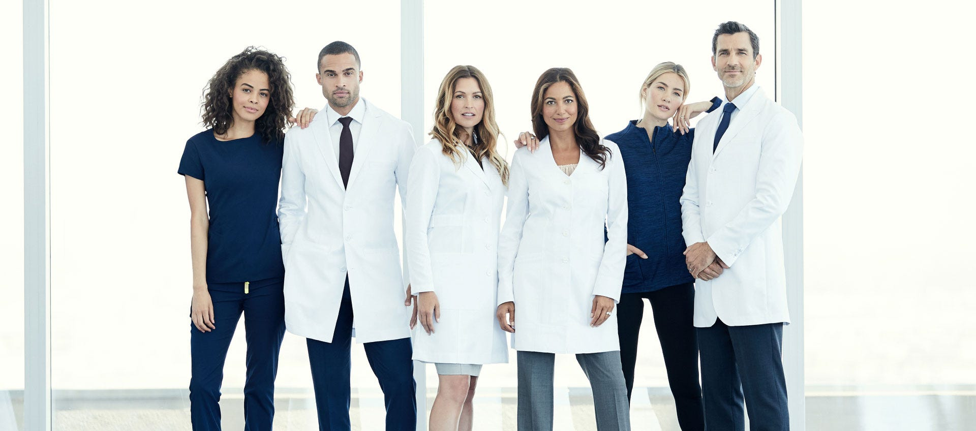 men and women standing together in scrubs and labcoats
